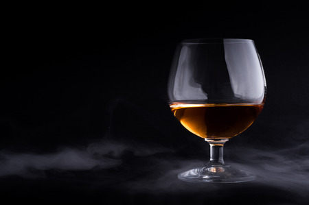 cognac: Photo of cognac glass in a smoke against black background Stock Photo