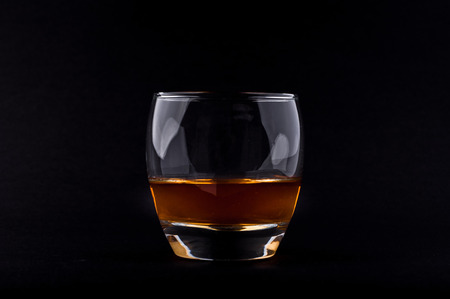 Photo of whisky glass against black background