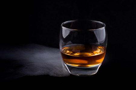 Photo of whisky glass in a smoke against black background