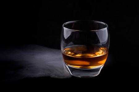 Photo of whisky glass in a smoke against black background Zdjęcie Seryjne - 39897613