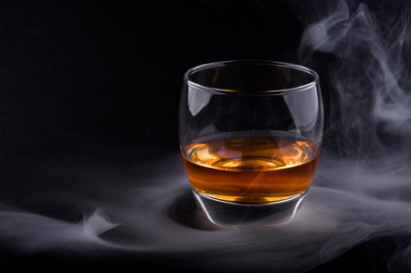 Photo of whisky glass in a smoke against black background photo