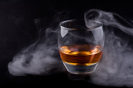 whisky glass: Photo of whisky glass in a smoke against black background