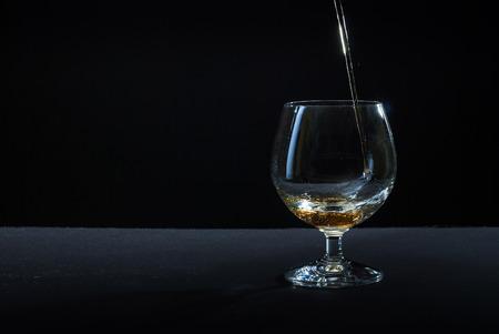 cognac: cognac in glass against black background