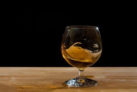 cognac: cognac glass on plank against black background