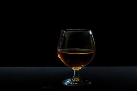 liqueurs: cognac in glass against black background