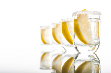 tomando alcohol: Photo of four shots of vodka with lemon