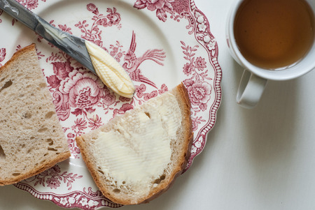 buttered: Photo of Tasty buttered bread on the vintage plate, with butter knife and tea on the white wooden table