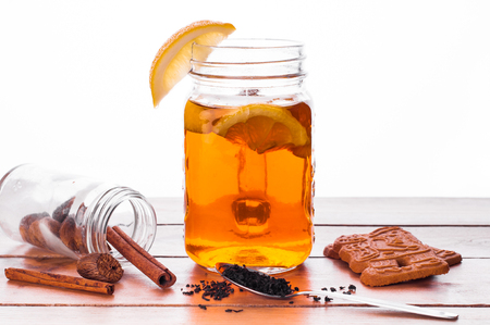 Photo of Hot spiced tea in jar on wooden table