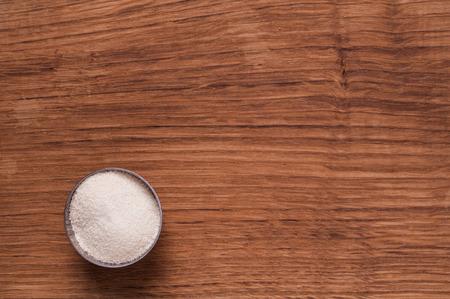 semolina: Photo of Semolina in metal bowl on brown wooden table