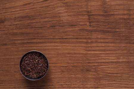 linseed: Photo of linseed in metal bowl on brown wooden table Stock Photo