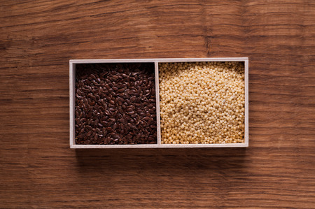 linseed: photo of linseed and millet in wooden box on brown wooden table - top view Stock Photo