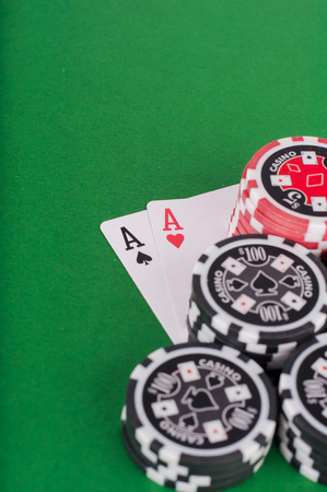 photo of aces pair, red and black cassino chips on green table