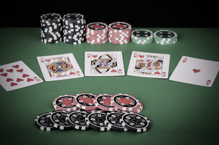 flush: photo of green casino table with royal flush, red and black chips - vintage