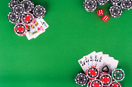 photo of top view of green casino table with royal flush, red and black chips