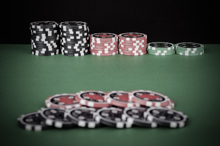 casino table: photo of green casino table with red and black chips - vintage