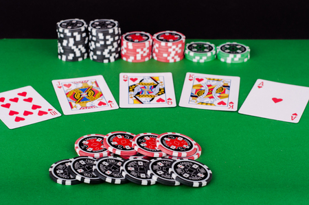 flush: photo of green casino table with royal flush, red and black chips Stock Photo