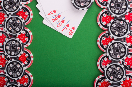 flush: photo of top view of green casino table with royal flush, red and black chips