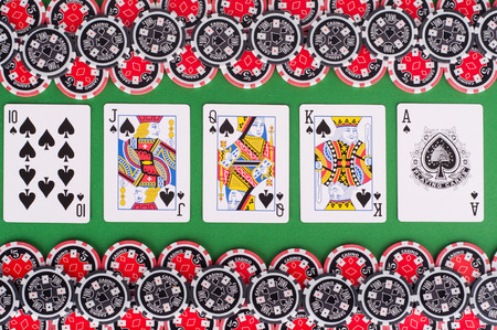 royal flush: photo of top view of green casino table with royal flush, red and black chips