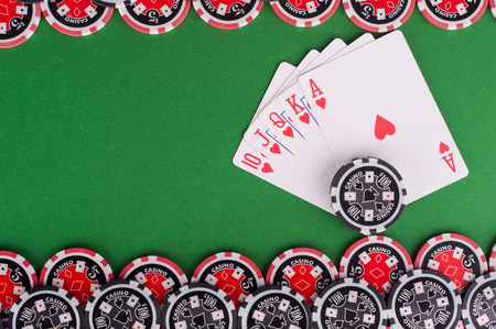 casino table: photo of top view of green casino table with royal flush, red and black chips