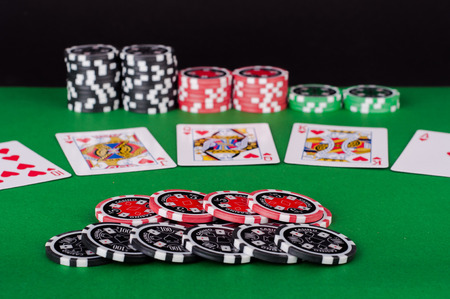 casino table: photo of green casino table with royal flush, red and black chips Stock Photo