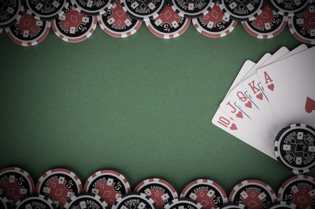 royal flush: photo of top view of green casino table with royal flush, red and black chips - vintage