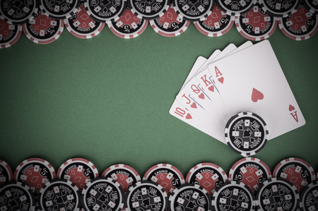 flush: photo of top view of green casino table with royal flush, red and black chips - vintage