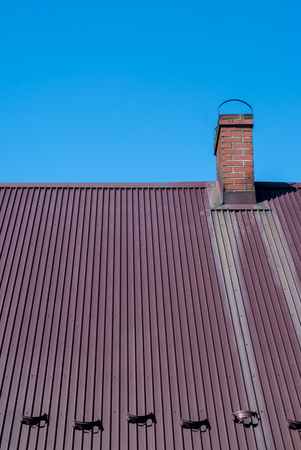 photo of metal roof with brick chimney - blue sky as background
