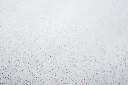 photo of raindrops on window glass with cloudy sky as background