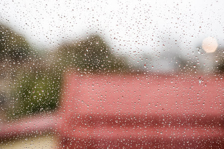 photo of raindrops on window glass with cloudy sky and city roofs as background Zdjęcie Seryjne
