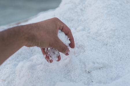 photo of One man picking up sea salt in his hand Zdjęcie Seryjne