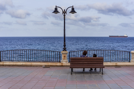 Photo of Two people sitting on bench and watching mediterranean sea, Valletta, Malta Zdjęcie Seryjne