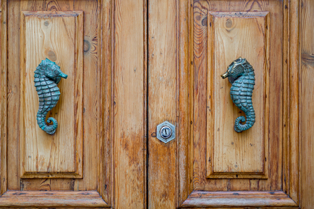 Photo of Traditional metal seahorse door handle on wooden door, Malta Zdjęcie Seryjne