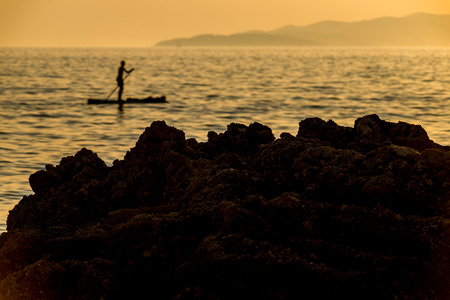 Photo of Silhouette of young couple on stand up paddle board. Active vacation, beach life.