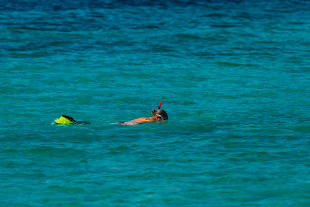 Photo of Vacation tourist, young person, snorkeling in paradise clear water. Snorkeler in crystalline waters . Turquoise sea background.