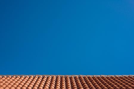 Zdjęcie dachu z czerwonej dachówki z niebieskim niebem w tle