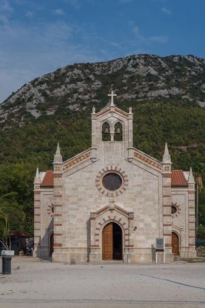 Photo of old church in Ston, Peljesac peninsula, Dalmatia, Croatia, with beautiful mountain and blue sky as background