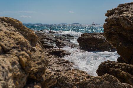 Photo of Waves breaking on a stony beach in Murter, Croatia, Dalmatia