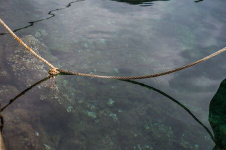 Photo of reflection in the sea of old boat and ropes in harbour