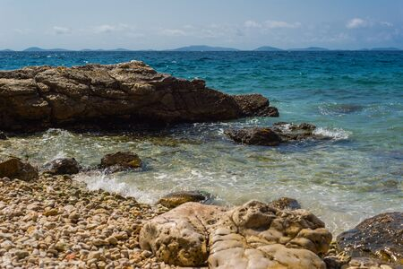 Photo of Waves breaking on a stony beach in Murter, Croatia, Dalmatia