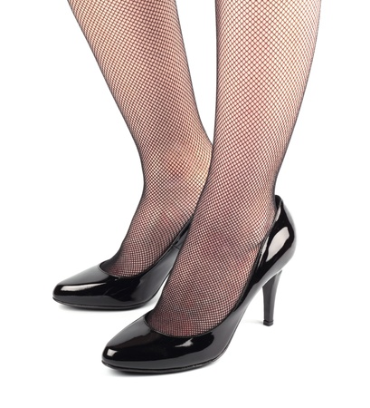 Girl legs in black patent leather female high heeled shoes isolated on white background photo