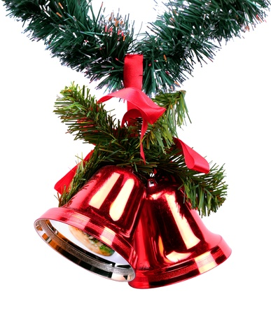 Two red Christmas bells with red ribbon and spruce branches on  green Christmas garland photo