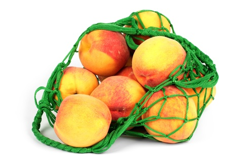 The peaches in a green string bag isolated on white background photo