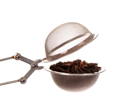 Black tea in strainer isolated on white background photo