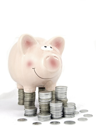 pink piggy bank feasting on column of coins