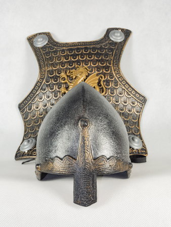 A medieval helmet with a nose shield and a breastplate decorated with the image of a dragon. Toy medieval, knight's equipment.