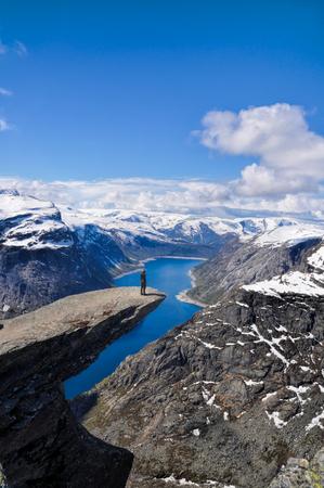 Hiker gazing at nature around Trolltunga rock in Norway
