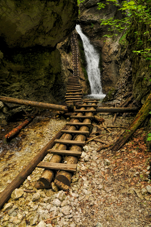 Picturesque view of a waterfall and wooden ladders in Slovak Paradise National Park photo