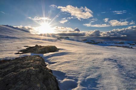Panoramic view of sun setting down over mountains near Trolltunga, Norway photo