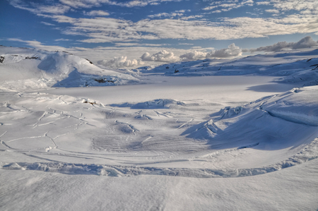 Panoramic view of deep cracks in the thick snow cover over a valley near Trolltunga, Norway photo