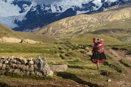 A Peruvian woman walking with a child on her back in South American Andes